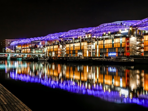 The shopping centre Confluence has a luminouus facade at night.